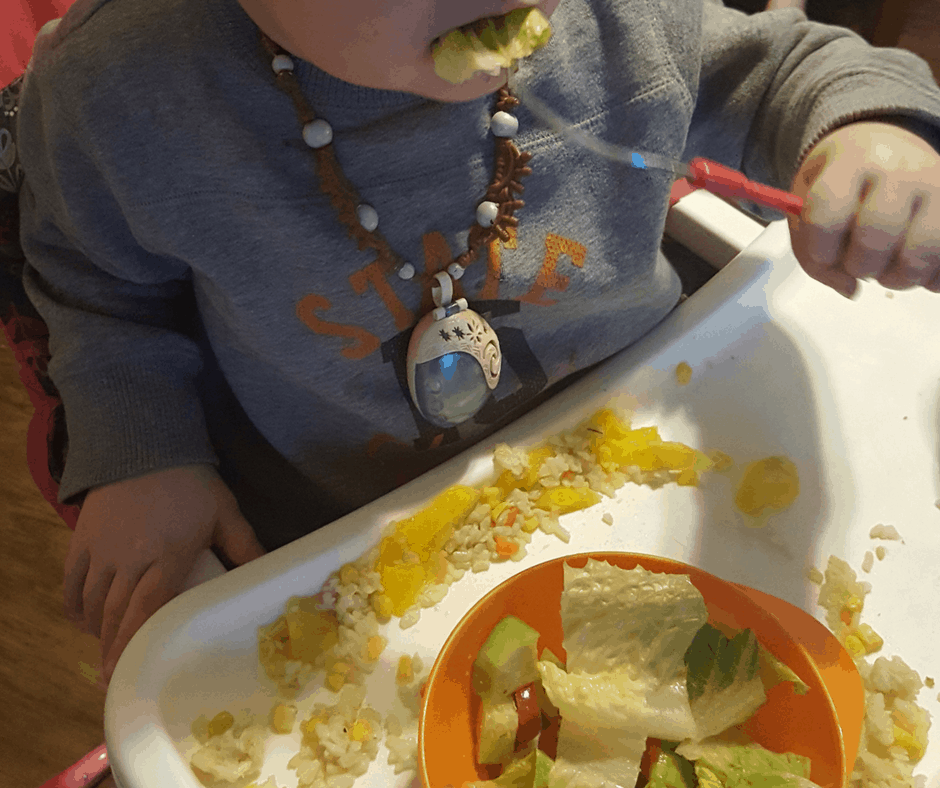get toddlers to eat veggies, toddler eating veggies, a salad, in highchair, wearing moana necklace